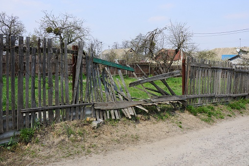 istock gray broken wooden plank fence in green grass on a rural street 1145673104