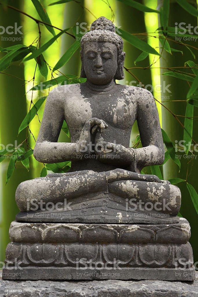 Gray Buddha statue with bamboo background stock photo