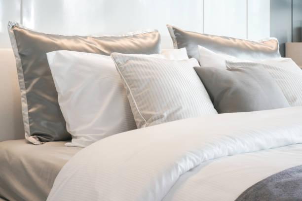 grijze kleur regeling kussens op bed met satijn klaar stijl beddengoed instellen - kussen beddengoed stockfoto's en -beelden