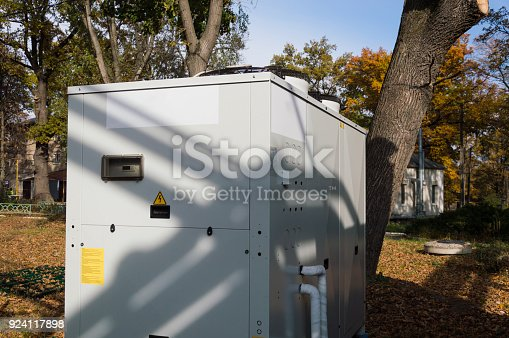 istock Gray commercial cooling unit for central ventilation standing outdoor on the ground covered by fallen leaves 924117898