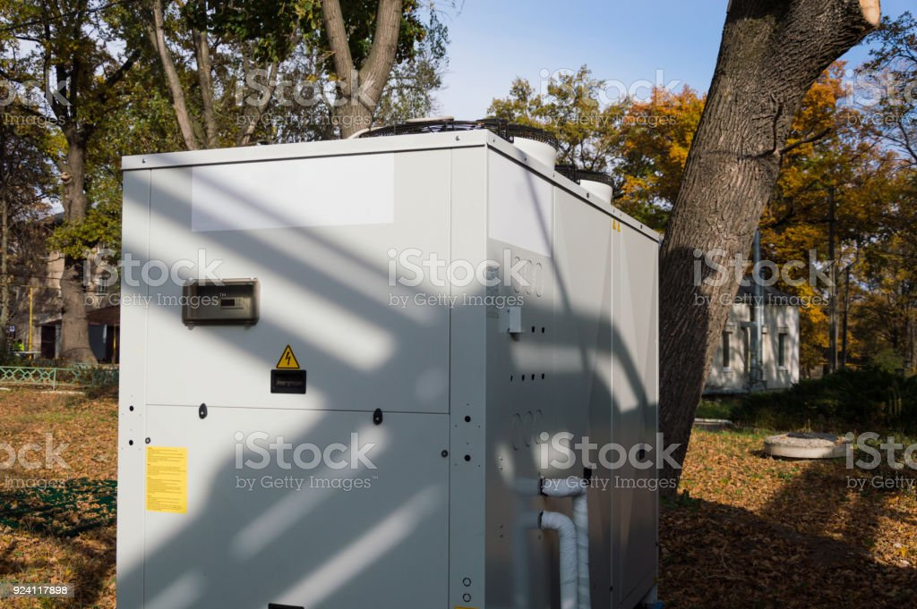 Gray commercial cooling unit for central ventilation standing outdoor on the ground covered by fallen leaves stock photo