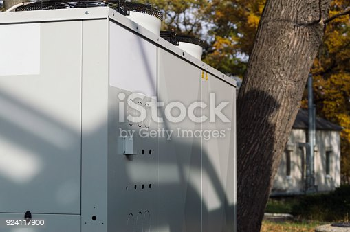 istock Gray commercial cooling unit for central ventilation system standing outdoor on the ground covered by fallen leaves 924117900