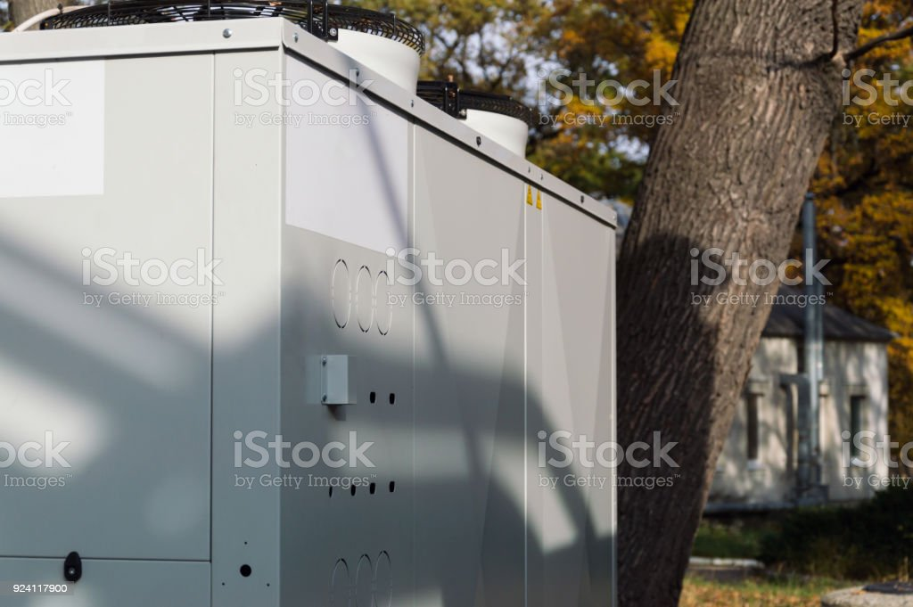 Gray commercial cooling unit for central ventilation system standing outdoor on the ground covered by fallen leaves stock photo
