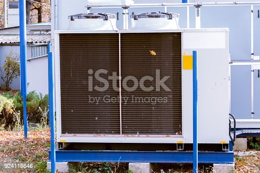 istock Gray commercial cooling unit for central ventilation system with big ventilation unit standing outdoor on the ground covered by fallen leaves 924116646