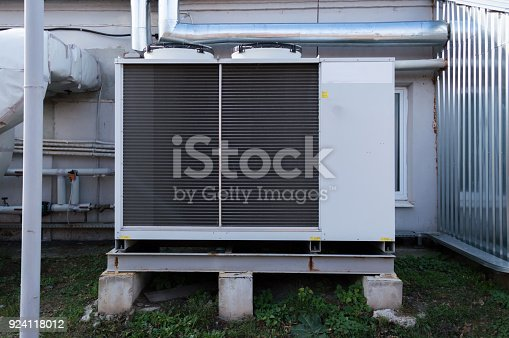 istock Gray commercial cooling unit for central ventilation system with big ventilation unit standing outdoor on the ground 924118012
