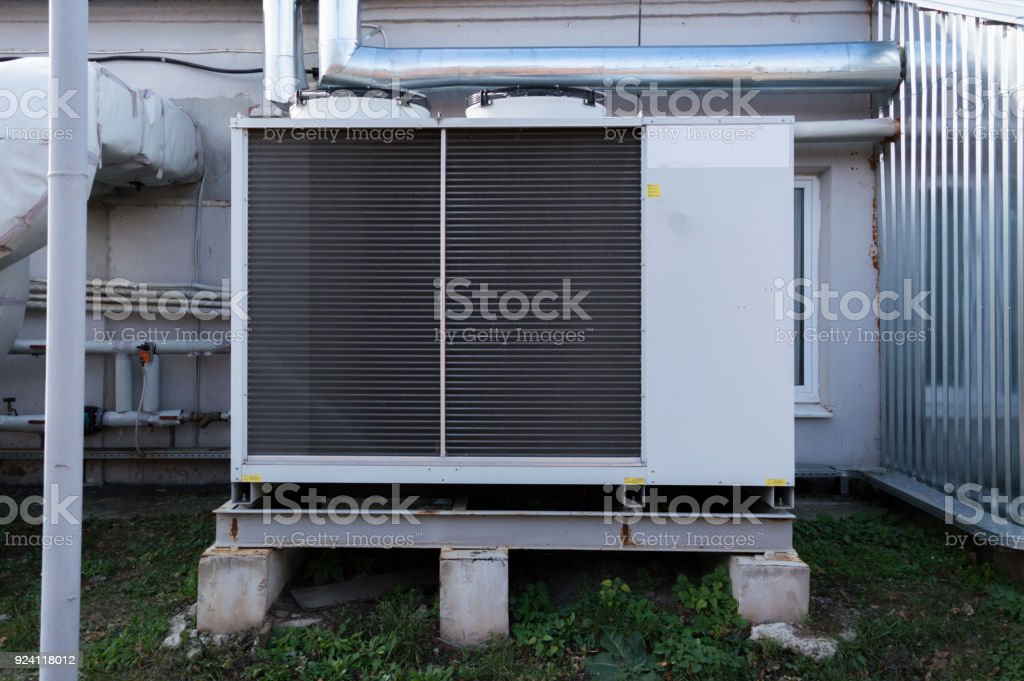 Gray commercial cooling unit for central ventilation system with big ventilation unit standing outdoor on the ground stock photo