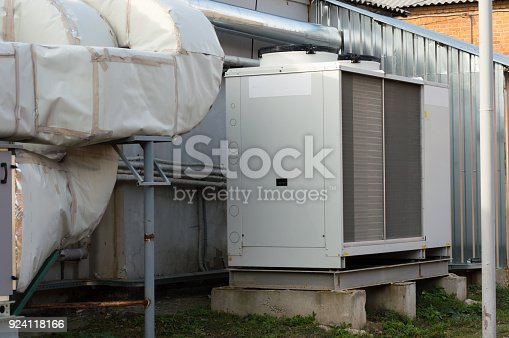 istock Gray commercial cooling unit for central ventilation system with big ventilation unit standing outdoor on the ground covered by fallen leaves 924118166