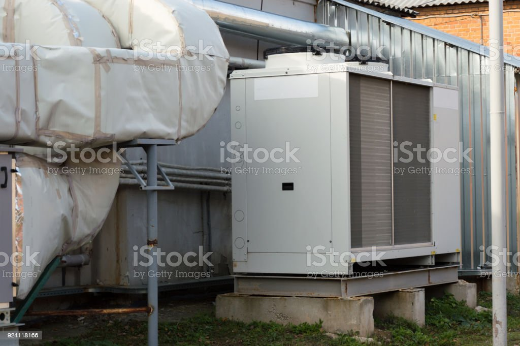 Gray commercial cooling unit for central ventilation system with big ventilation unit standing outdoor on the ground covered by fallen leaves stock photo