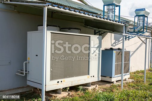 istock Gray commercial cooling unit for central ventilation systemstanding outside under the roof 924118018