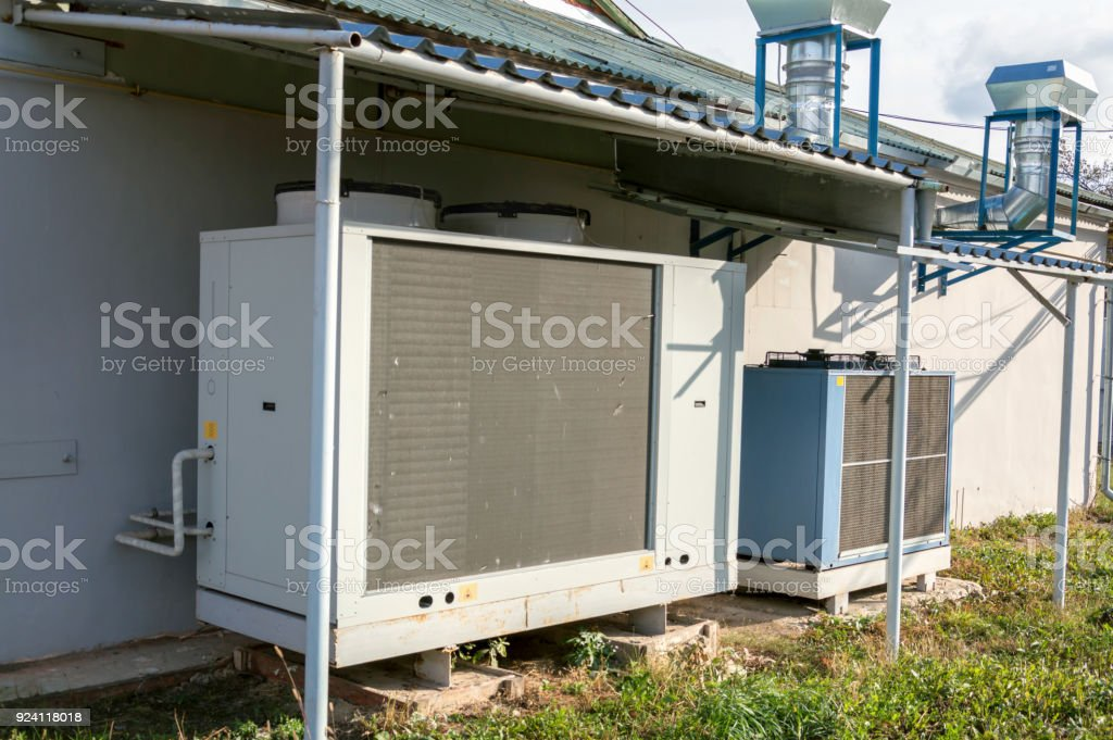Gray commercial cooling unit for central ventilation systemstanding outside under the roof stock photo