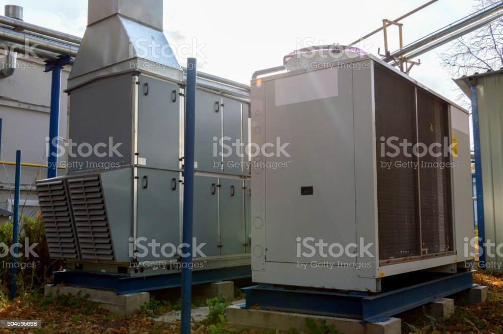 Gray commercial cooling unit with big commercial ventilation unit standing outdoor on the ground covered by fallen leaves stock photo