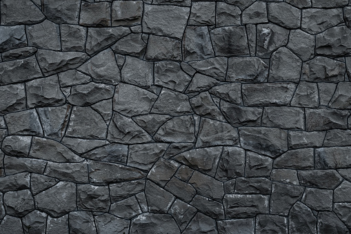 Gray dirty stone wall. Texture of grey granite. Dark rough rocks background. Weathered dark gray grunge building's facade. Stone surface. Mosaic pattern of grey stones on the cement wall. Old dirty wall rock texture. Grey backdrop of decorative tiles.