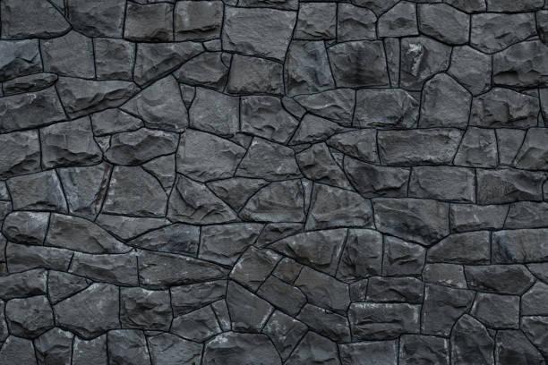 灰色骯髒的石牆。灰色花崗岩的紋理。深粗糙的岩石背景。風化的深灰色的粗野建築的外觀。石材表面。水泥牆上灰色石頭的馬賽克圖案。舊的骯髒的牆體岩石紋理。裝飾瓷磚的灰色背景。 - 大廈樓層 個照片及圖片檔