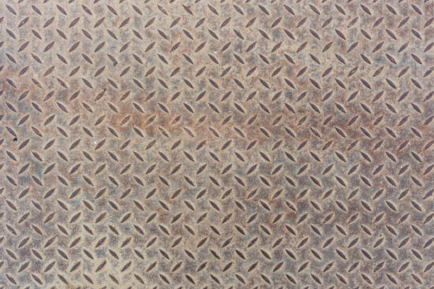 Gray dusty flat heavy metal sheet floor texture with diamond or checker or tread skid proof pattern. Background and texture. stock photo