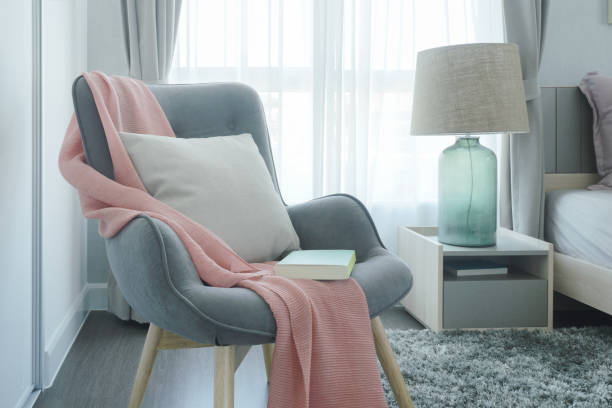 Gray easy armchair with pink scarf, pillow and book next to bed in the bedroom Gray easy armchair with pink scarf, pillow and book next to bed in the bedroom armchair stock pictures, royalty-free photos & images