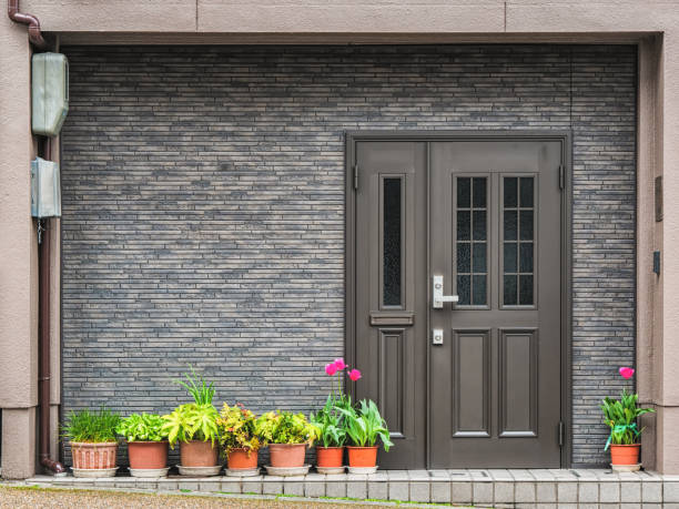 Gray front door with small square decorative windows and flower pots in fron of it Gray front door with small square decorative windows and tiled concrete wall with flower pots in fron of it front door stock pictures, royalty-free photos & images