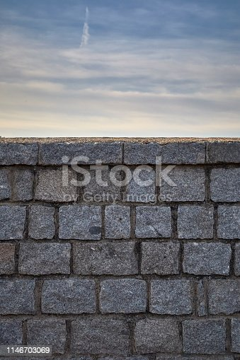 gray granite stone wall under a blue sky