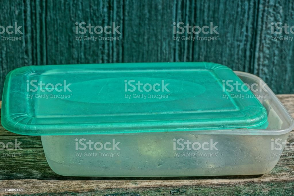 one gray green plastic empty food box on wooden table
