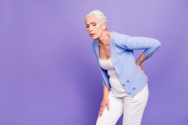 gray haired old beautiful  woman wearing casual suffering from back pain. empty blank copy space. isolated over violet pastel background - osteoporosi foto e immagini stock