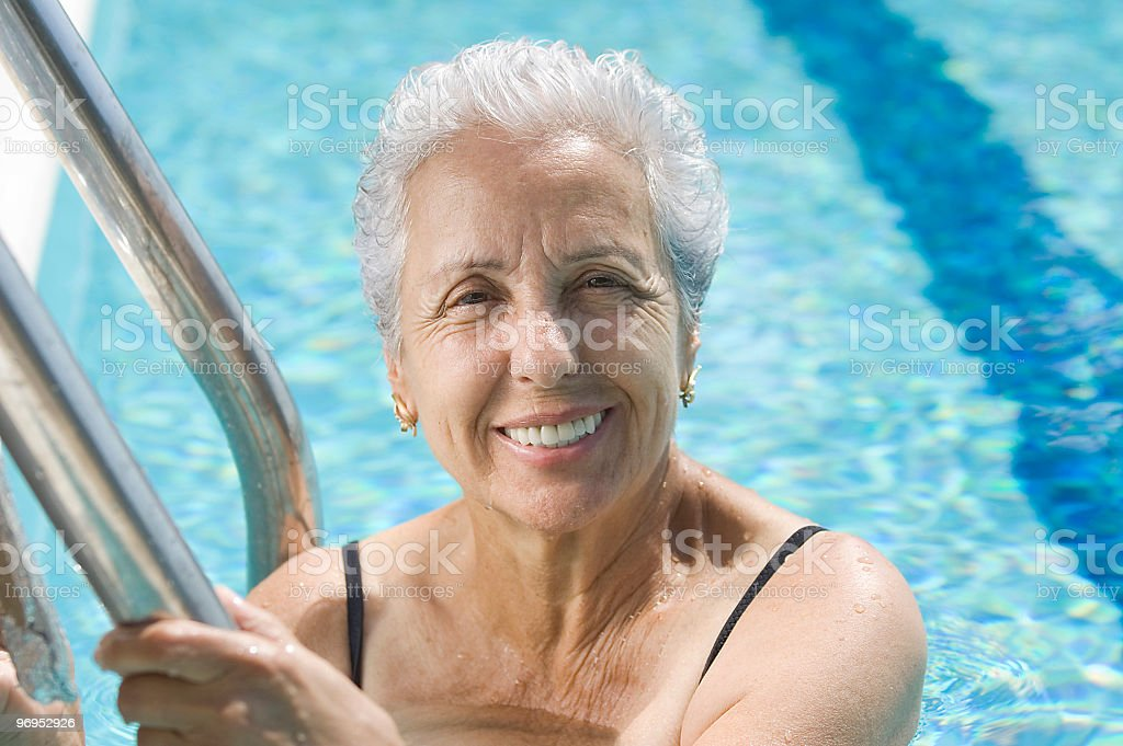 Gray haired woman in swimming pool holding onto metal ladder royalty-free stock photo