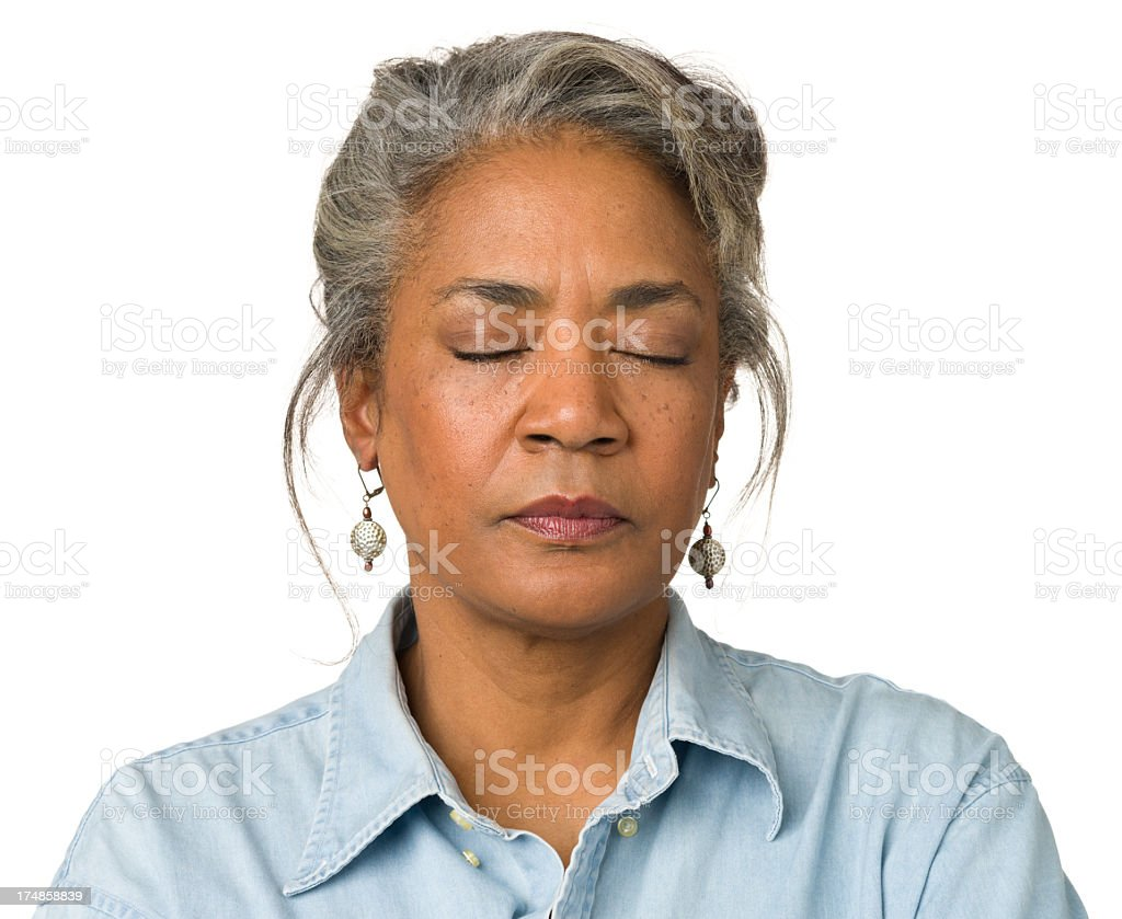 Gray haired woman wearing droplet earrings with eyes closed stock photo