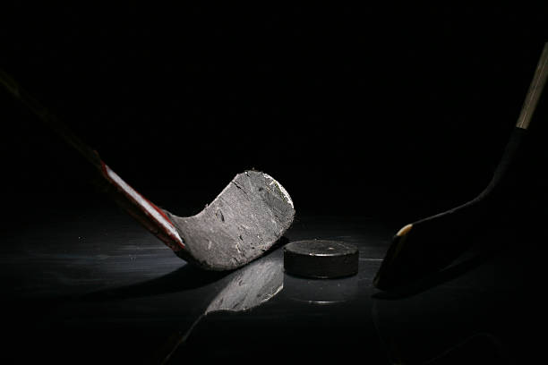 a gray hockey stick and a puck in solitude - hockey stick stock pictures, royalty-free photos & images