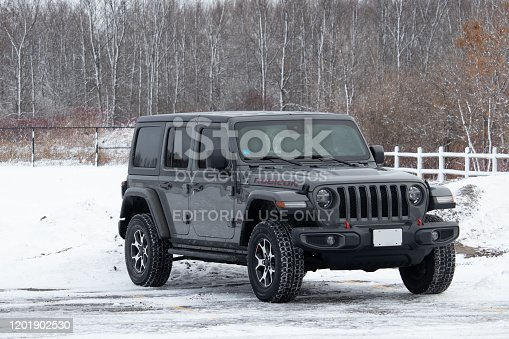 DECEMBER 16, 2019 - OTTAWA, ONTARIO, CANADA: A late model Jeep Wrangler JL Unlimited Rubicon off-road SUV, first seen in the 2018 model year, is parked in a snowy parking lot before trees in winter.