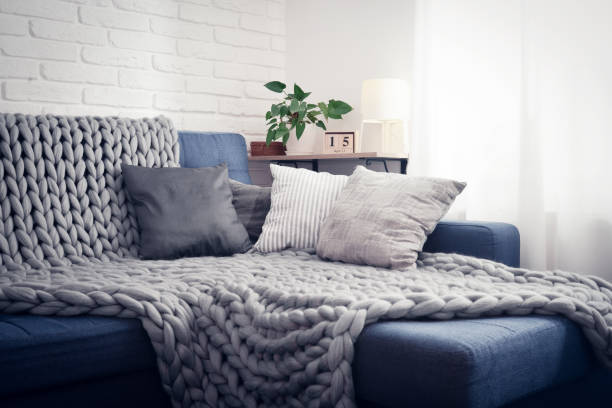 Gray knitted blanket from merino wool Gray knitted blanket from merino wool on couch with pillows in the interior of the living room cozy stock pictures, royalty-free photos & images