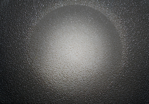 Gray Matted grained sphere on the black grained shiny background.