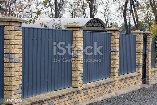 istock gray metal fence and brown bricks 1187974220