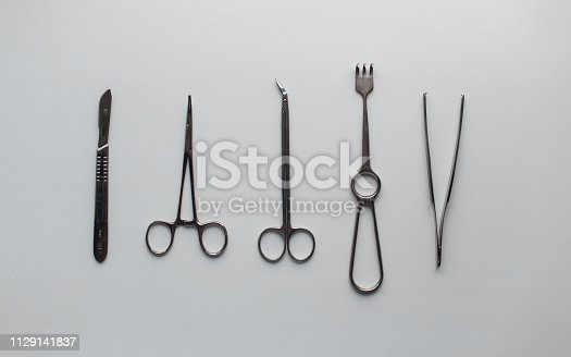 Gray metal medical instruments for neurosurgery on a white table in the operating room. View from above.