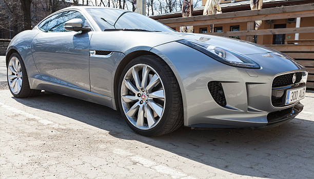 Gray metallic Jaguar F-Type coupe, closeup Tallinn, Estonia - May 2, 2016: Gray metallic Jaguar F-Type coupe, closeup. Two-seat sports car, based on a platform of the XK convertible, manufactured by British manufacturer Jaguar Cars from 2013 jaguar car stock pictures, royalty-free photos & images