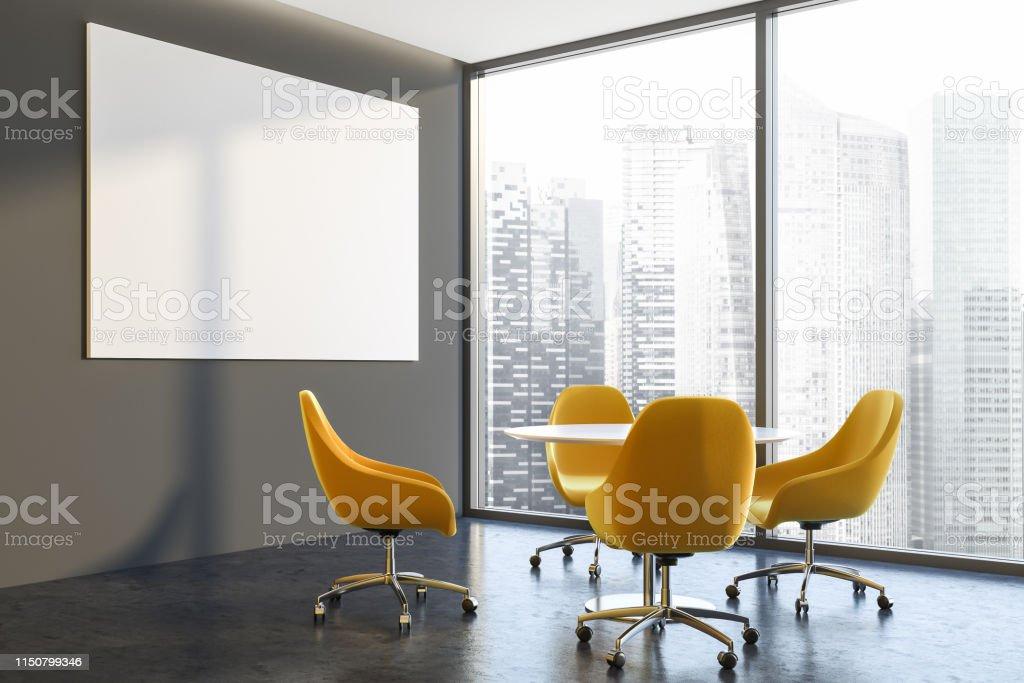 Corner of office waiting room with gray walls, concrete floor,...