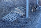 istock gray old broken fence from wooden boards in the wall overgrown with dry vegetation and grass 1203260622