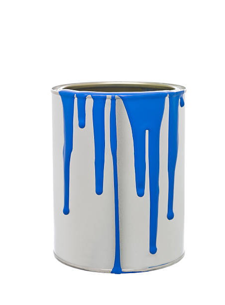 Gray paint can with bright blue paint spilling down the side stock photo