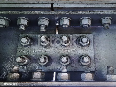 Close-up Gray Painted Metal Connecting Plates Joining Steel Frames with Group of Bolts and Nuts