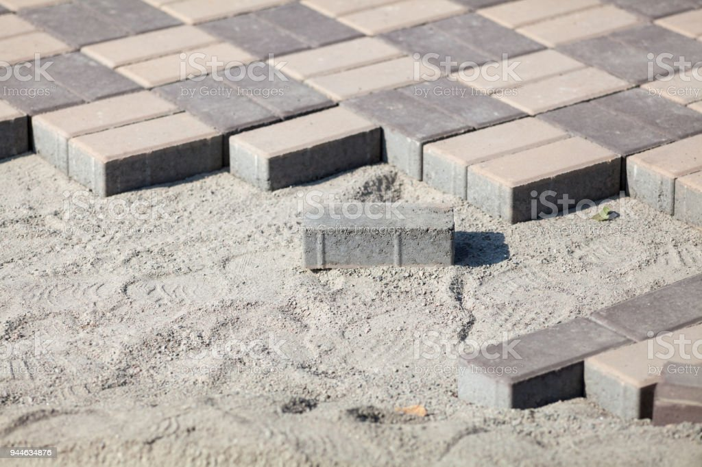 Gray paving blocks - side view. New sidewalk with rectangular stones on sandy ballast. Paving tiles in the process of laying. stock photo