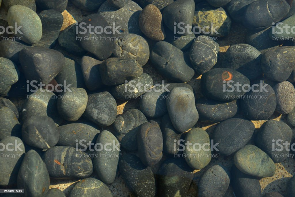 Gray pebble stones background with water stock photo