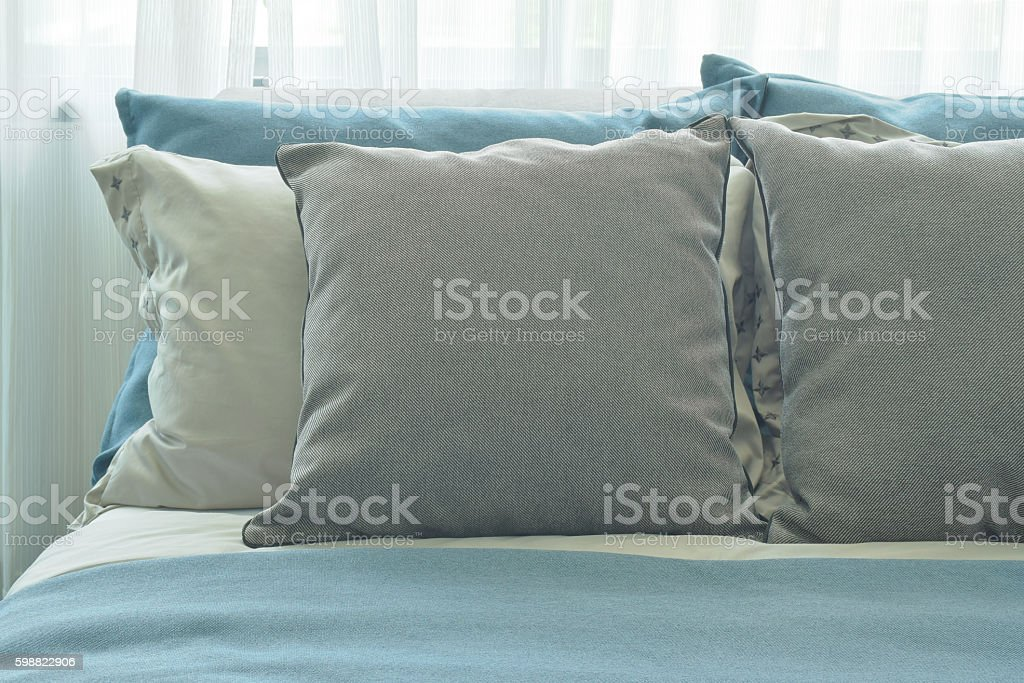 Gray pillows setting on blue color scheme bedding stock photo