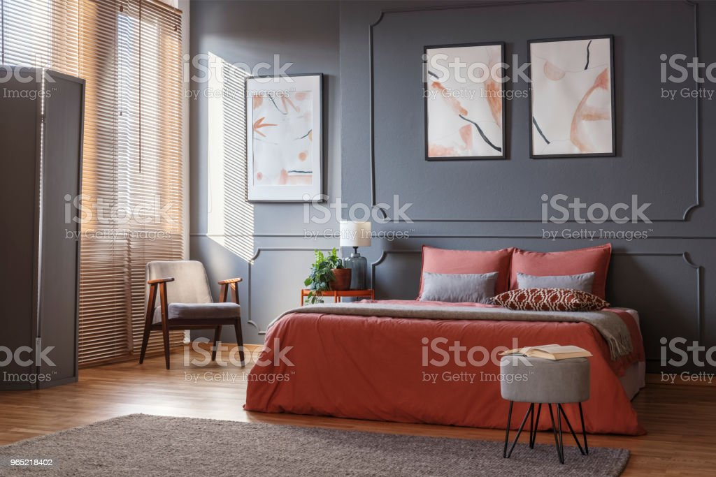 Gray, retro armchair standing in the corner of an elegant bedroom interior with watercolor posters on dark gray wall with molding and orange sheets on the bed. Real photo zbiór zdjęć royalty-free