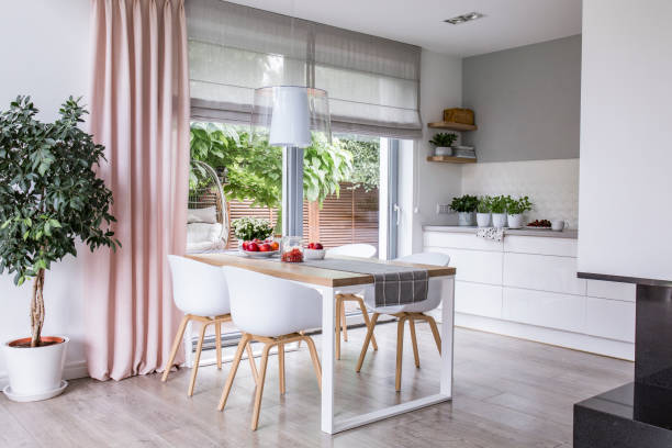 gray roman shades and a pink curtain on big, glass windows in a modern kitchen and dining room interior with a wooden table and white chairs - curtain stock pictures, royalty-free photos & images