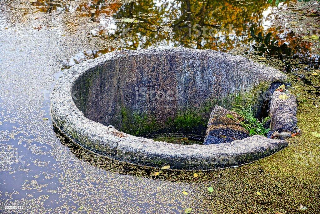 Gray round concrete dam on the lake stock photo
