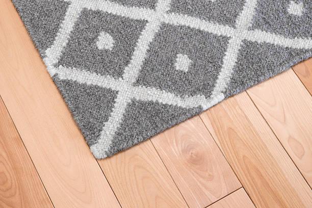 Gray rug on wooden floor stock photo