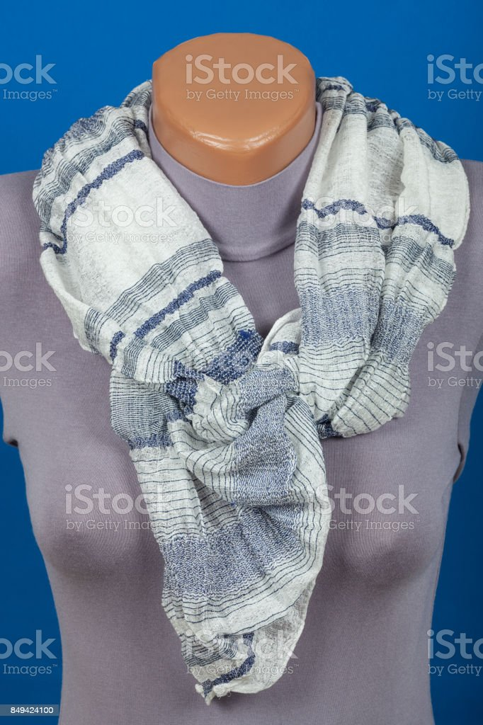 Gray scarf on mannequin isolated on blue background stock photo
