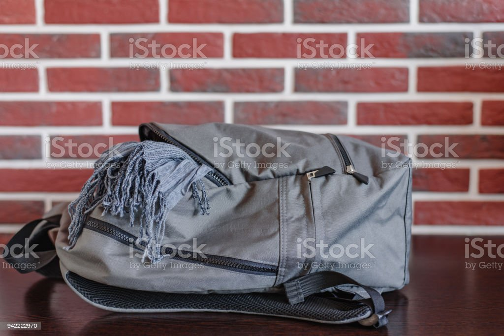 Gray school backpack and scarf on a red brick wall background – zdjęcie