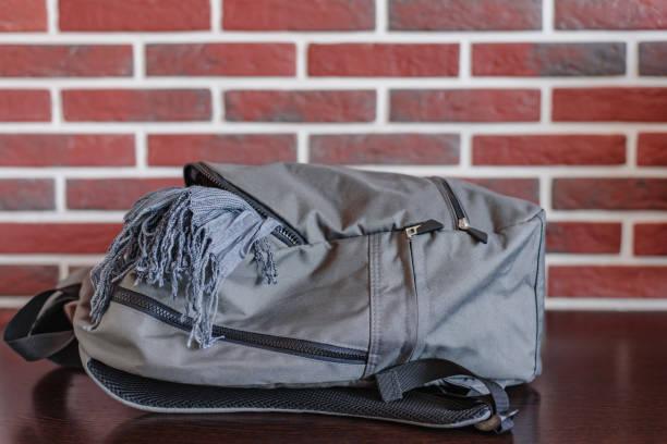 gray school backpack and scarf on a red brick wall background - back to school zdjęcia i obrazy z banku zdjęć