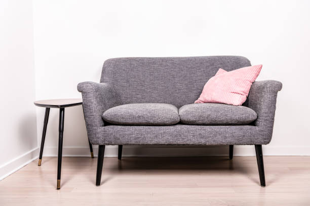 gray settee with a pink pillow sitting stock photo