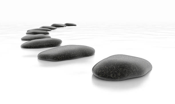 Gray stepping stones across shallow water stock photo