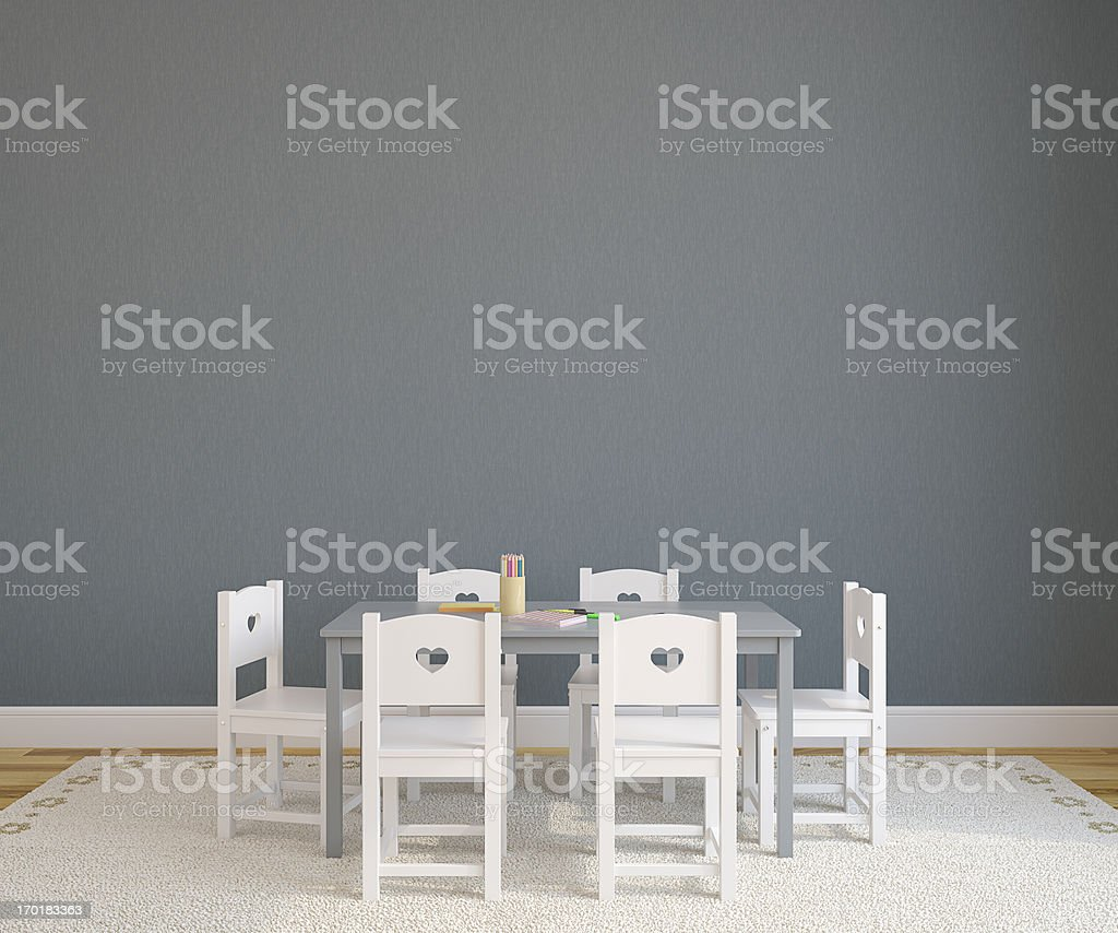 A gray table with six white chairs in a playroom stock photo