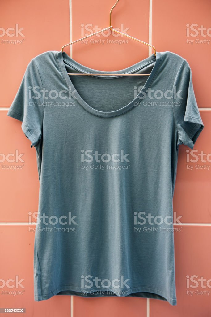 Gray tee hanging on the wall stock photo